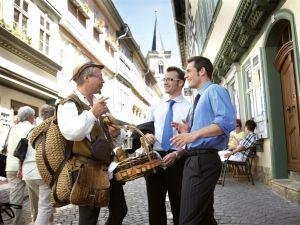 Erfurt: Geschäftsmänner mit Brezelhändler auf der Krämerbrücke (Foto: Guido Werner/Thüringen Tourismus)
