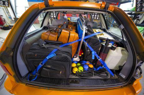 Die Ladung wird mit Spanngurten korrekt gesichert; schwere Gepäckstücke sind unten, dirket hinter der Rücksitzbank